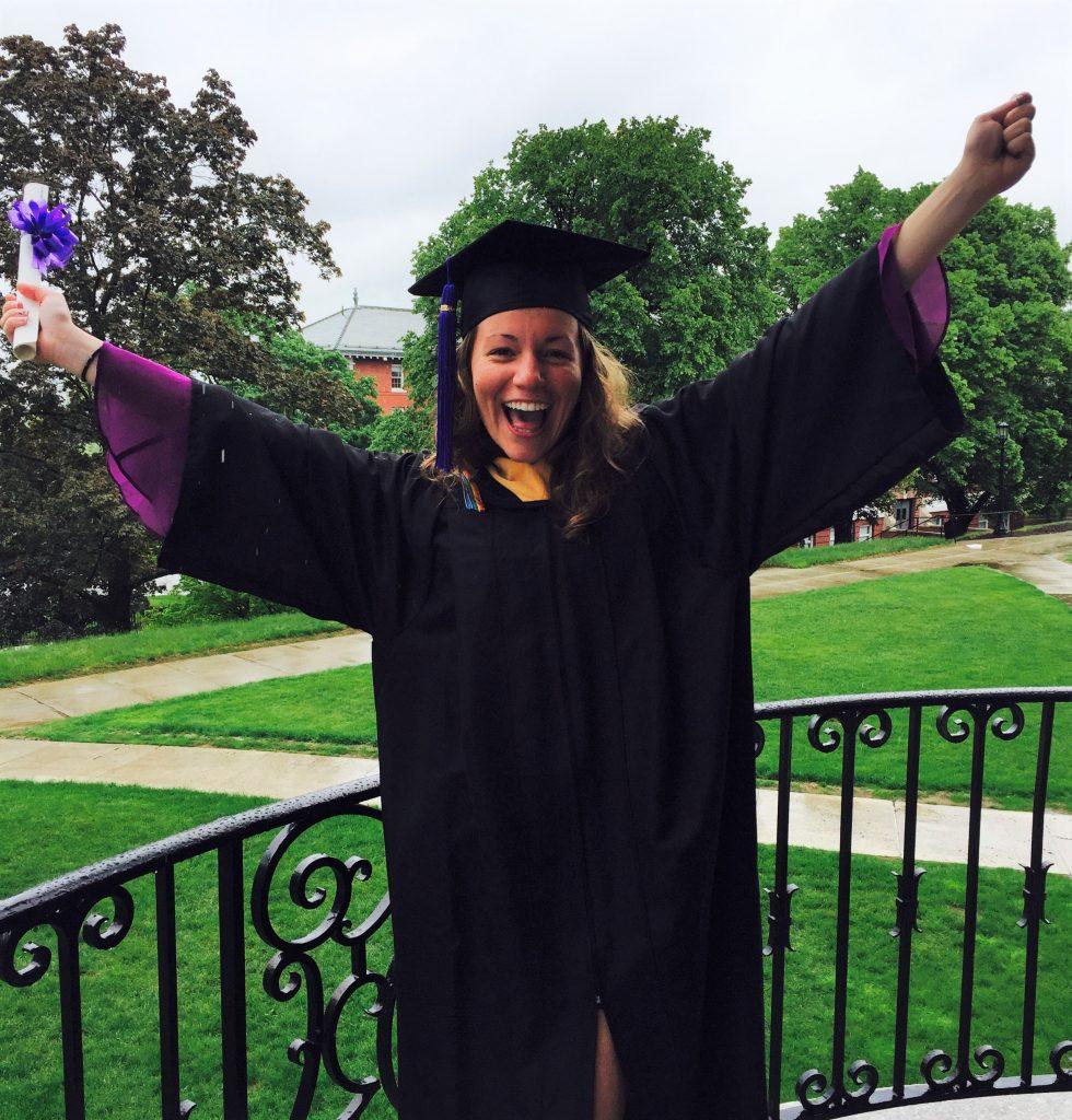 Smiling woman in graduation attire.